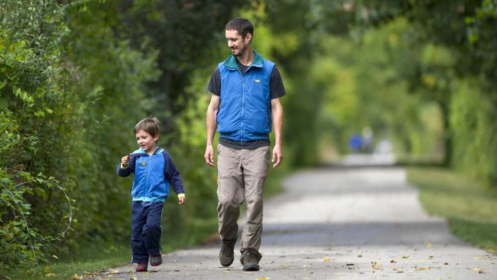A father and son walk on the trail.