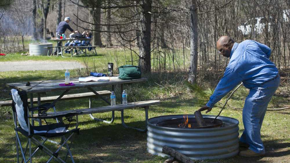 Man tends a fire at his camp site