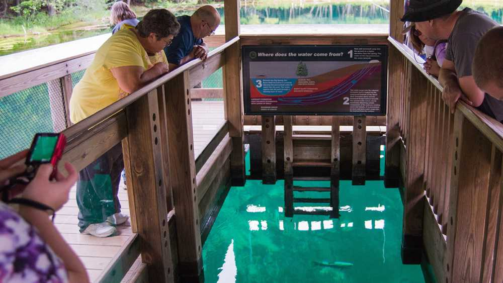 People look over the interior raft railing to view fish swimming in Kitch-iti-kipi spring.
