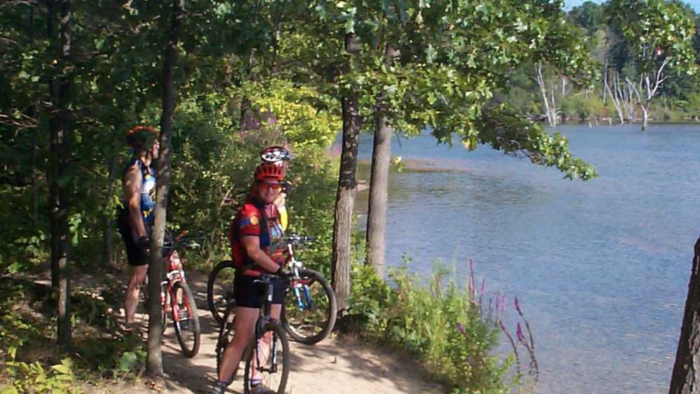 Bicyclists stopped on the pathway along side Eagle Lake.