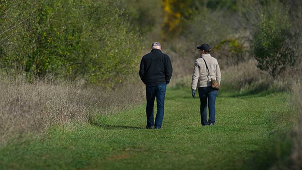 Two people walk a trail at  Watkins Lake State Park and County Preserve