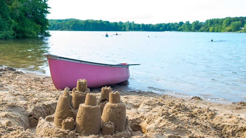 A sand castle near a pink canoe on the beach.