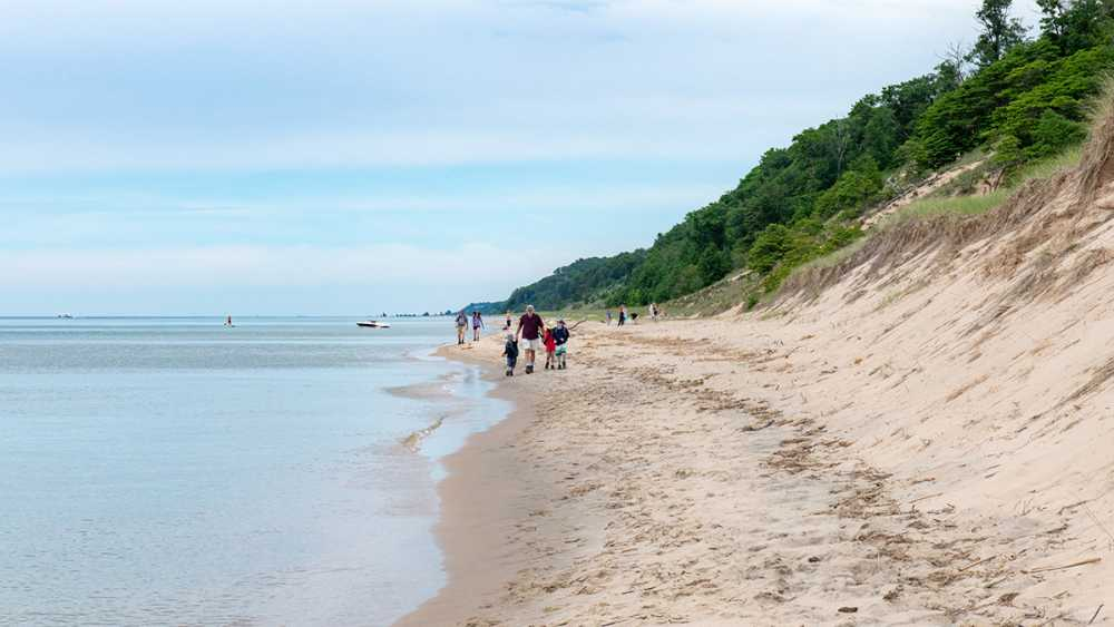 People walk the sand beach at Saugatuck Dunes State Park.