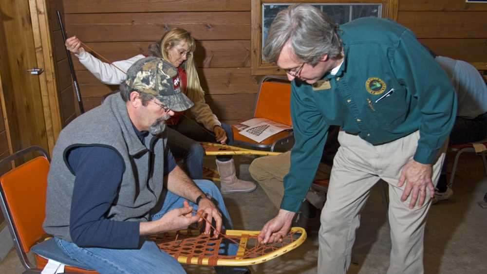 People learning to make snow shoes with instructions from a DNR educator