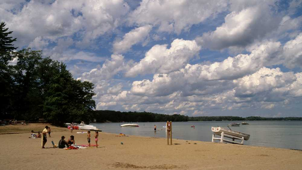 People swimming and sunbathing on the beach at Interlochen State Park