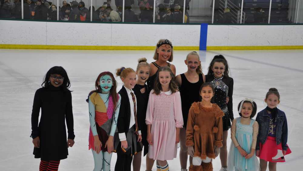 Members of the Muskegon Lakeshore Figure Skating Club pose after their Halloween on Ice Show