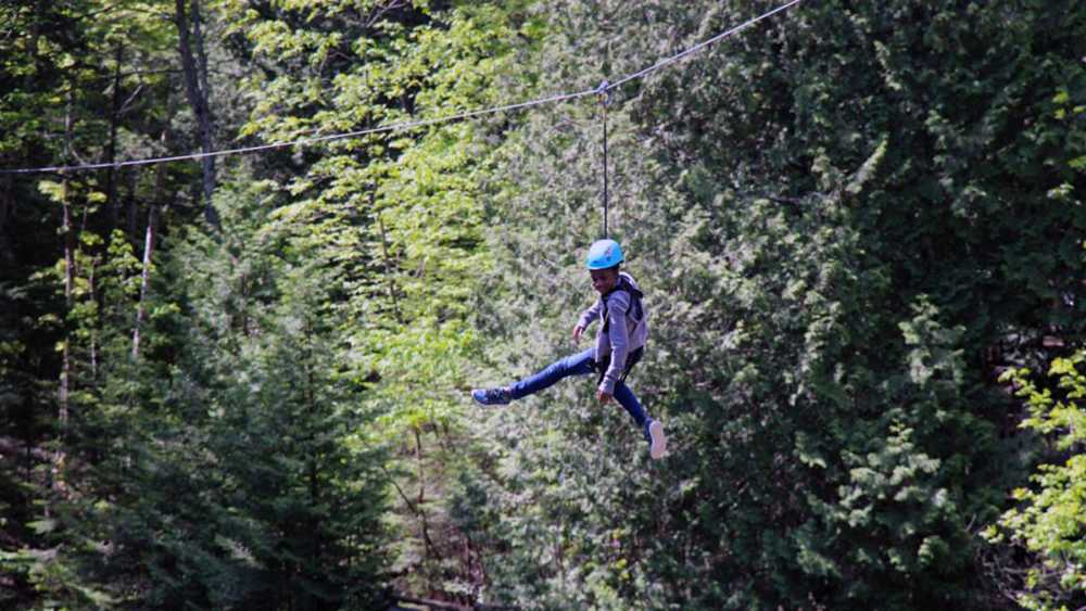 Smiling kid on zipline at Historic Mill Creek Discovery Park in Mackinaw City
