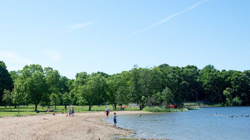 Children playing on a wide sandy beach at Island Lake Recreation Area