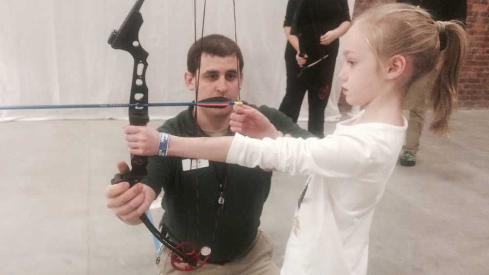 Young girl trying archery at the OAC archery range.