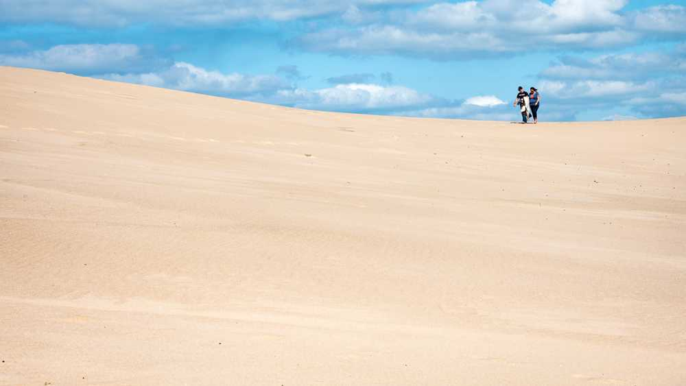 Two people walk the dune at Silver Lake State Park