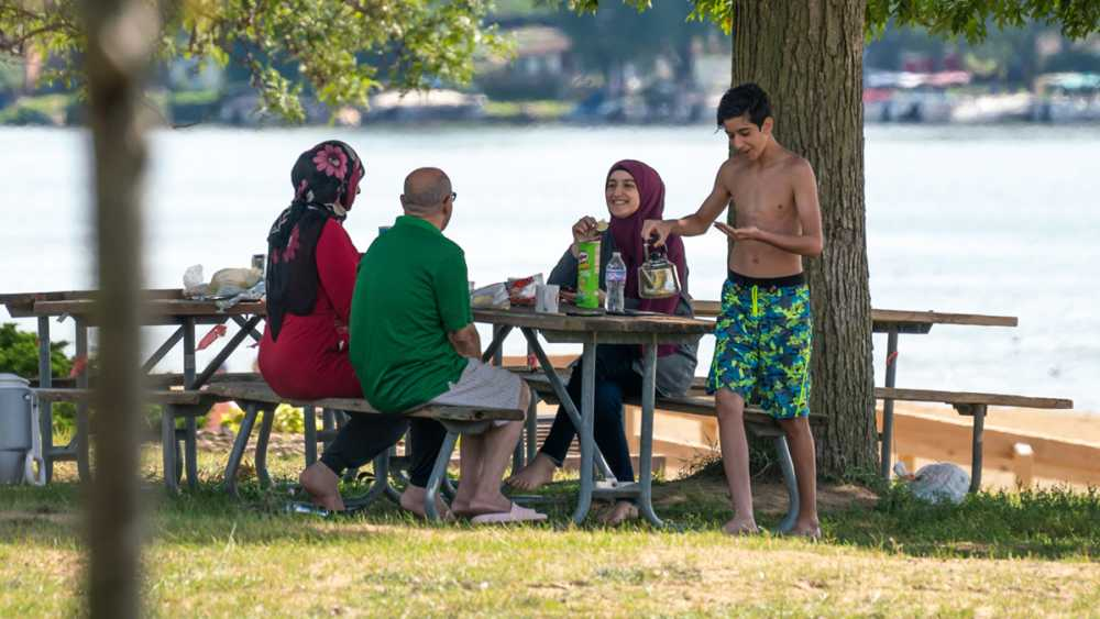 A family sits at a picnic table near the lake on a summer day.