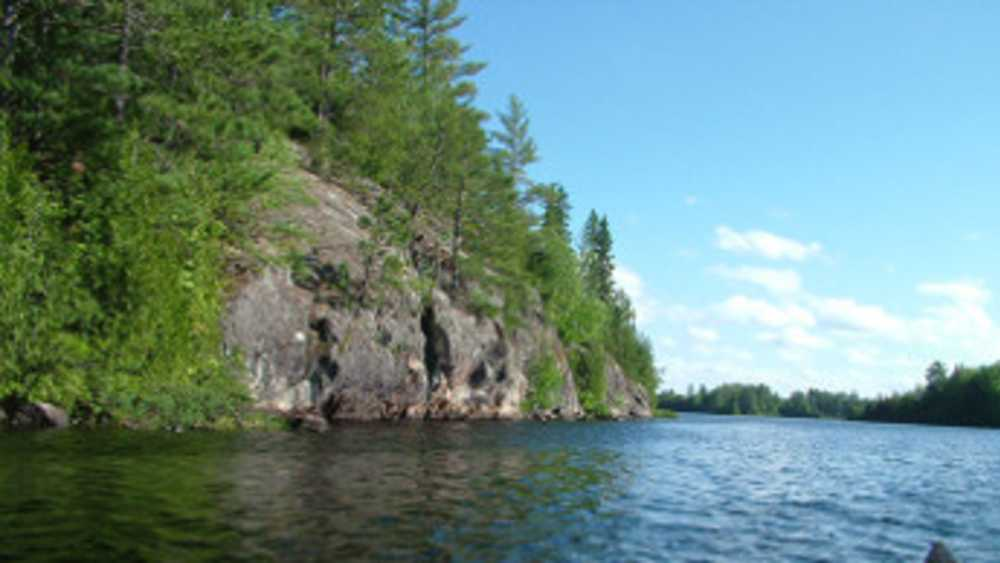 Craig Lake with a view of a rocky shoreline covered with trees.