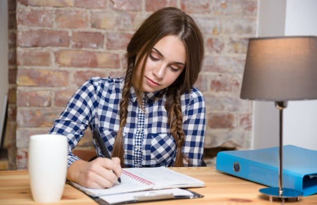 Portrait of a young woman doing her homework at home