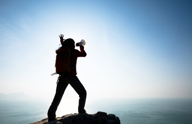 Young woman shouting with loudspeaker on windy sunrise coast cliff edge