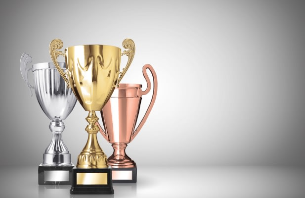 golden, silver and bronze trophies on gray background
