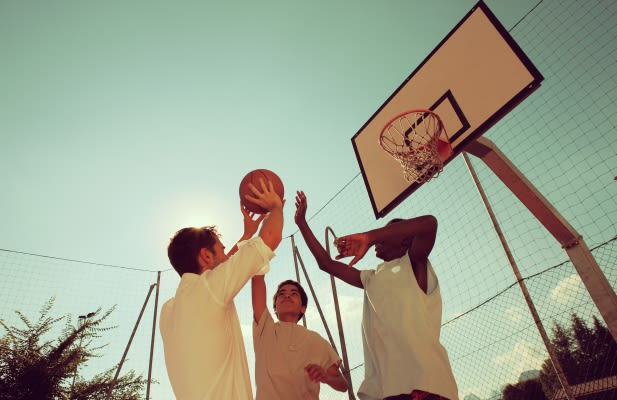 Two Afro-American boy and a man playing basketball