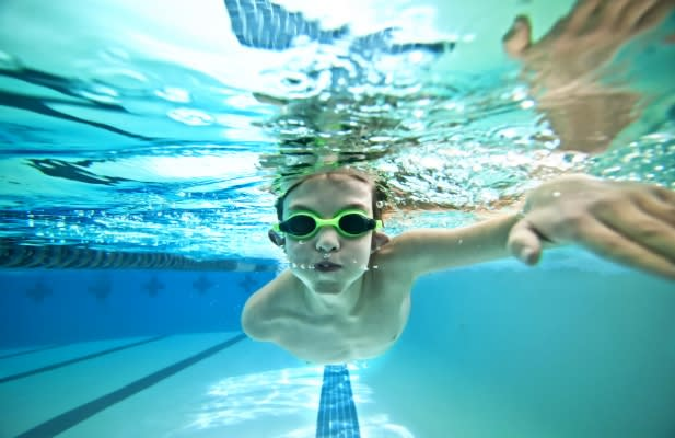 underwater shot of boy swimming laps in pool