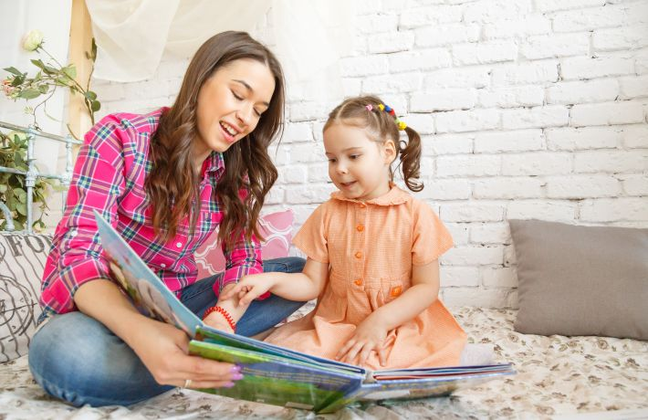 Young mother and her child girl reading a book.