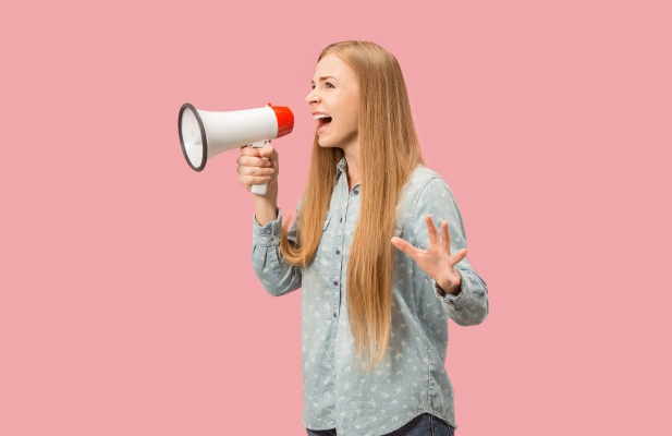 Woman making announcement with megaphone at pink studio