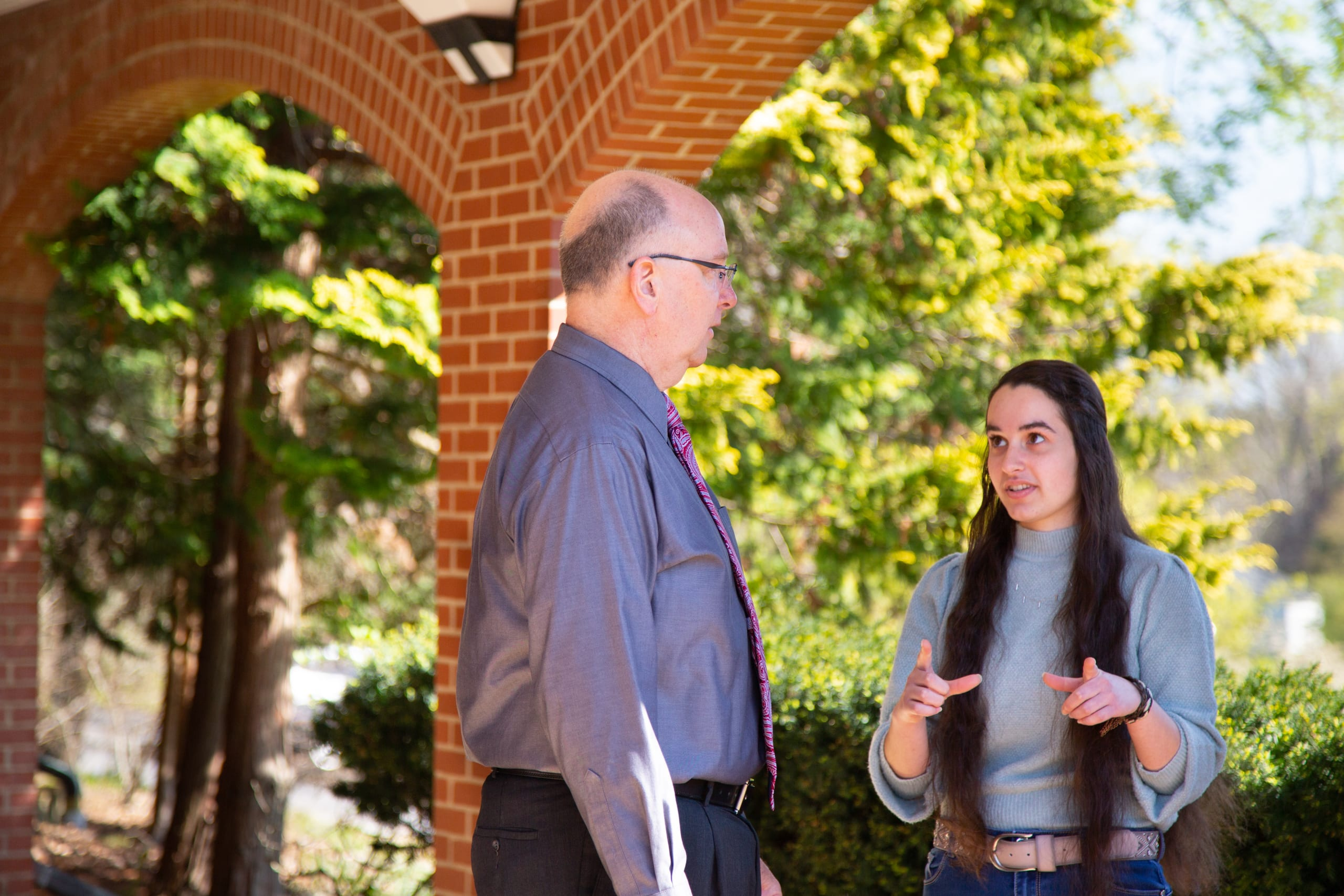 Accounting professor Bob Mahan talks with student after class.