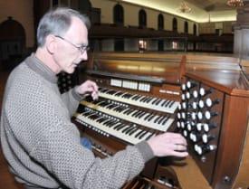 Dr. David Runner sits at the organ console.