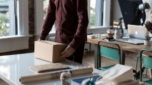 A man dressed in a long sleeved dark red shirt readies a package while his studio is in the background