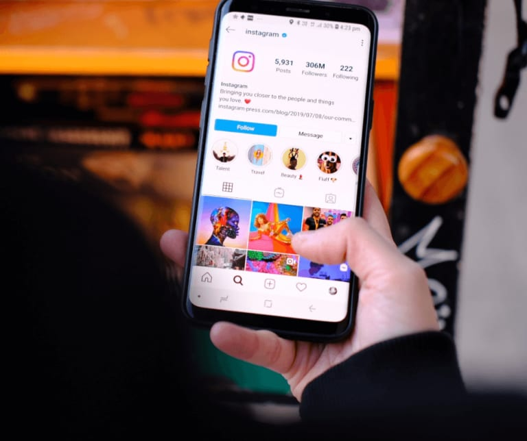 A white person holds a phone. Only the right thumb and phone are shown, with the screen showing an instagram page and photos of the beach