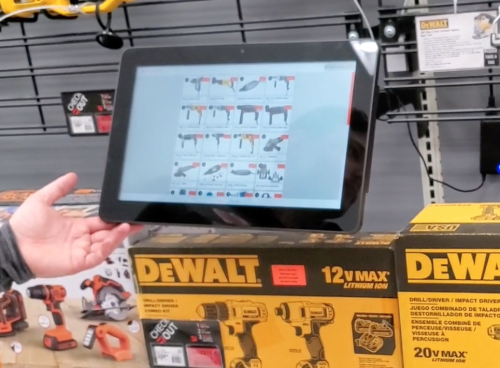 Customer uses an in-store display to browse items to buy.