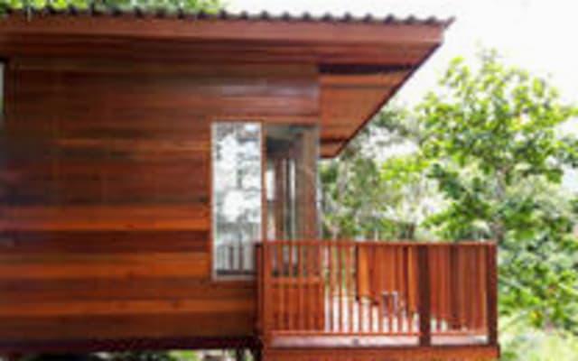 Kleiner Holzbungalow mit Ventilator und Gartenblick
