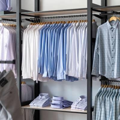 A wall display of shirts on racks.