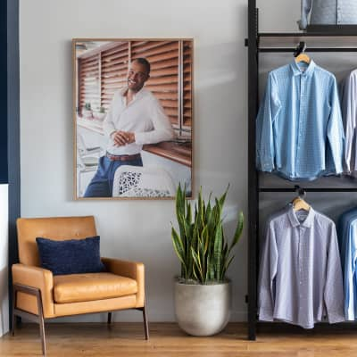 A wall of the store, featuring racks of shirts, a large model photo, chair, and plant.