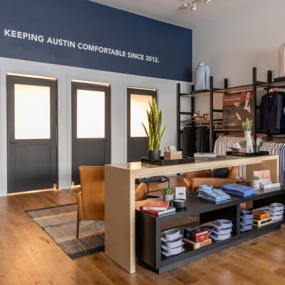 The interior of the store, featuring a display of folded dress shirts and dressing rooms.