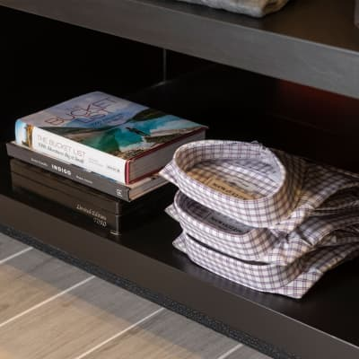 A closeup of a drawer with folded dress shirts.