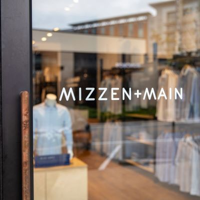 A closeup of the Mizzen+Main logo on the storefront window.