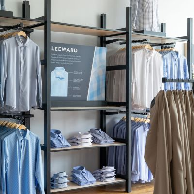 A wall display of shirts on racks, along with a prited sign with info about our shirts.