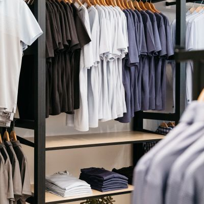A wall of the store featuring folded and hung shirts.