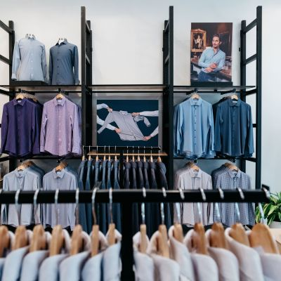 The interior of the store, showing many racks of dress shirts.