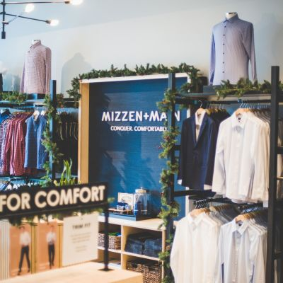 An in-store display, featuring the Mizzen+Main logo, surrounded by racks of clothing.