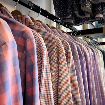 A closeup shot of a row of shirts on hangers.