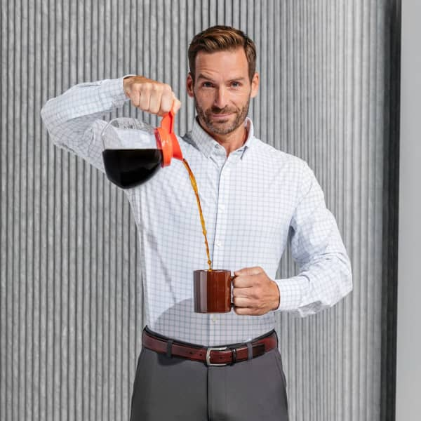 A man, wearing Mizzen+Main clothes, pours coffee into a mug, while grinning at the camera.