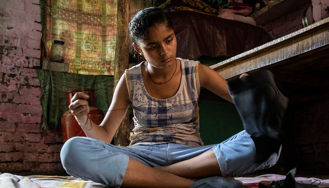 Anu spends hours each day hand stitching leather for shoes