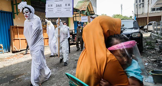 Endonezya'da maske takmayanlara ilginç cezalar uygulanıyor