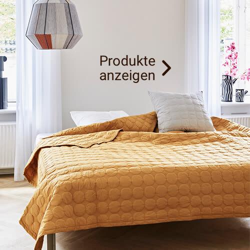 Bett im Skandi Stil mit gelber Decke