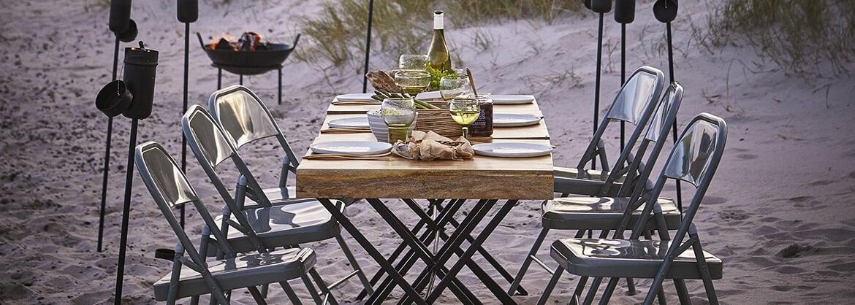 Gemütlicher Esstisch mit Stühlen am Strand