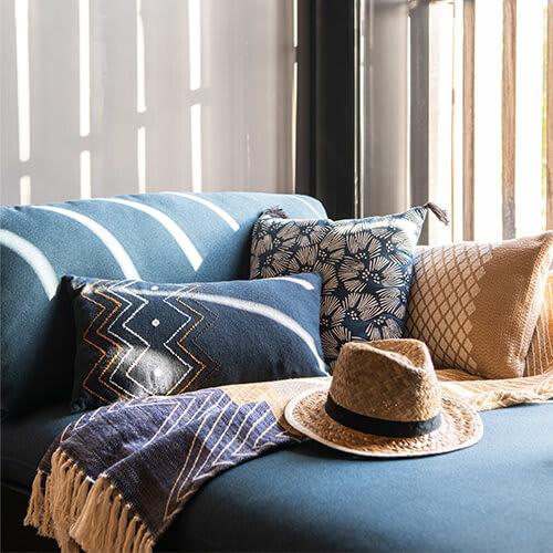 Mediterranes blaues Sofa mit Kissen und Decke