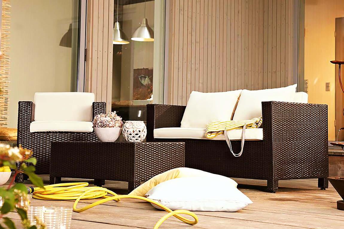 Loungemöbel aus Rattan mit hellen Kissen