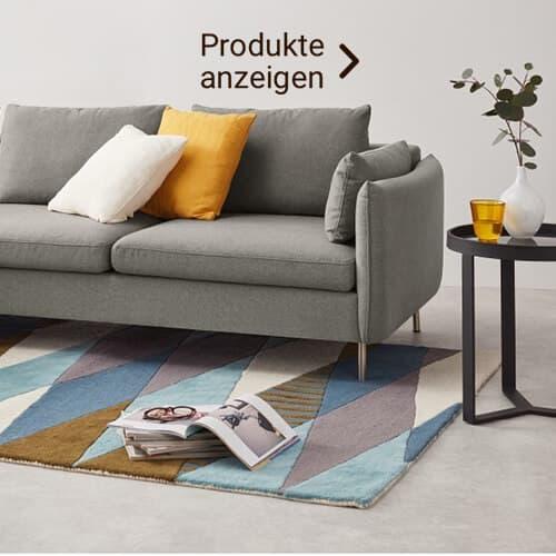 Graue Couch im Skandi Stil mit bunten Kissen
