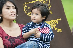[Person with chin length dark hair wears a scoop neck red shirt and holds a young child with short dark hair carrying a small US flag. ]