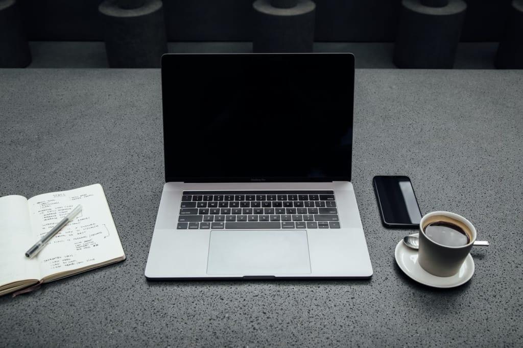 Ordinateur portable avec carnet, smartphone et tasse de café à côté