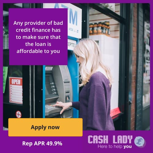 Lady in a purple jumper taking money from an ATM on the street